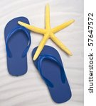 Summer Flip Flop Sandals with a Bright Yellow Starfish on a Sand Background. - stock photo