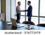 two smiling businessmen shaking ... | Shutterstock . vector #576771979
