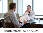 two focused coworkers sitting... | Shutterstock . vector #576772024
