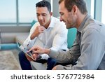 two smiling male work coworkers ...   Shutterstock . vector #576772984