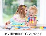 little boy and girl draw... | Shutterstock . vector #576976444