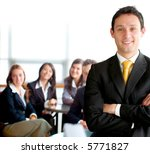 business man leading a team in an office environment smiling - stock photo
