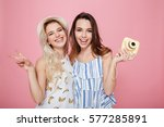 Small photo of Two cheerful lovely young women standing and holding photo camera over pink background