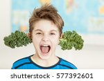 Small photo of Young boy sprouting fresh kale leaves from his ears yelling at the camera in a spoof on the concept of a healthy diet and nutrition