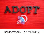 Small photo of Word ADOPT and passifier on color wooden background