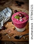 Small photo of Acai berry smoothie with cherries, walnuts, oat bran, greek yogurt and edible flowers.
