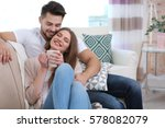 young couple sitting on sofa at ... | Shutterstock . vector #578082079