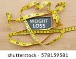 Small photo of Words WEIGHT LOSS written on chalkboard with measuring tape on wooden background. Concept of weight loss, weight management,changing to healthier lifestyle,weight loss health issue and social issue