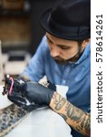 Small photo of Concentrated tattooist painting adornment on client arm