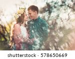 Small photo of Love and tenderness. Beautiful young loving couple looking at eath other and smiling in blossom spring garden. Romantic dating.