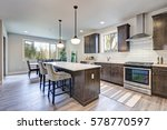 Stock photo new kitchen boasts dark wood cabinets white backsplash subway tile and over sized island with 578770597