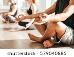 Stock photo closeup of african young man sitting and meditating in lotus pose with group 579040885