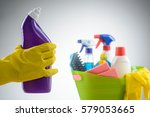Small photo of Hand in a latex glove holding a toilet cleaning liquid detergent, close-up. Container with all-purpose sprays, liquid detergents, kitchen cloths and a scrubber brush. Blurred background.