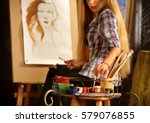 Small photo of Artist painting on easel in studio. Girl paints portrait of woman with brush. Female painter seen from behind. Indoor home interior for handmade crafts.