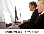 Two professionals working on computers - stock photo