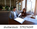 Small photo of Two business partners accounting data information about success of corporation using laptop, internet connection while sitting in modern coffee shop