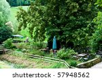 Beautiful garden with wooden fence, small river and bridge plus several chairs, tables and umbrellas - stock photo