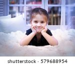 happy child lying on the bed.... | Shutterstock . vector #579688954