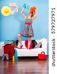 Small photo of Cleaning in the closet, fashion, happiness concept. Woman standing on sofa throwing up lot of clothes. Clothing flying all over the place