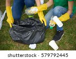 Small photo of Young woman holding black bin bag while her friend putting plastic household waste into it, close-up shot