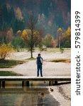 Small photo of Man standing on a wooden pond, admiring nature in Slovenia, Lake Jasna. Kranjska Gora.