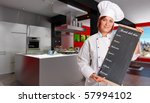 Woman with chef attire holding a blackboard with weekly menu in a modern domestic kitchen - stock photo