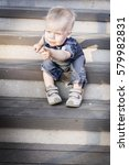 Small photo of Accusatory one and half year old child, a boy, sitting at stairs, looking with interested at something on steps and showing it expressively his finger. Industrial background.
