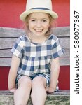Small photo of portrait of an adorable blonde little girl smiling cheekily in summer clothes and a hipster hat