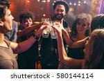 Stock photo group of friends having drinks at the night club party young people enjoying at a bar toasting 580144114