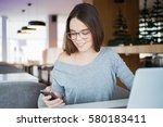 smiling young woman texting... | Shutterstock . vector #580183411