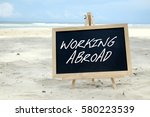 Small photo of WORKING ABROAD. Chalkboard with written message and beautiful beach background.