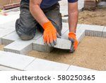 hands of a builder laying new... | Shutterstock . vector #580250365