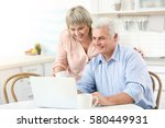 middle aged couple with laptop... | Shutterstock . vector #580449931