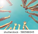 Small photo of Winner team with a cup, bottom view, background of the bright sky