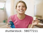 Small photo of A young woman shows off her teeth while holding a bottle of mouthwash. Horizontal shot.
