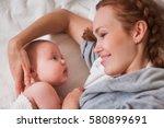 mom feeding baby | Shutterstock . vector #580899691