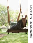 A Young Woman Is Swinging On A...