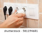 electrician hand plugging a... | Shutterstock . vector #581194681