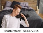 Stock photo happy young handsome caucasian man sitting with a black cat playing with pet at home love 581377315