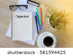 Small photo of Business concept - Top view notebook writing Objective