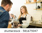 cute female barista giving... | Shutterstock . vector #581675047