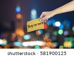 hand holding a buy or rent sign ... | Shutterstock . vector #581900125