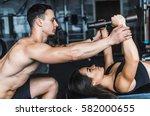 trainer helps a girl doing... | Shutterstock . vector #582000655