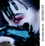 Small photo of Portrait of a woman in cold tones. Girl with bright makeup closes his hand on the person who runs the black acrylic paint