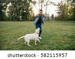 Stock photo man throwing ball to dog labrador in park at sunset best friends playing in ball 582115957