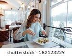 smiling woman eating fresh... | Shutterstock . vector #582123229
