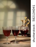 Small photo of Two antique glasses filled with claret with decanter in the background