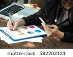 Small photo of Business woman is writing on business paper with computer notebook and holding mobile phone in left hand