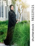 Small photo of Excellent business day. Arab businesswomen in hijab is the street Dubai while smiling and looking straight in camera. The woman is dressed in a black abaya