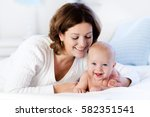 mother and child on a white bed.... | Shutterstock . vector #582351541